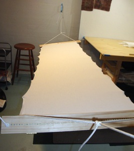 Stretched fabric, with shinshi on underside, harite (fabric clamps)