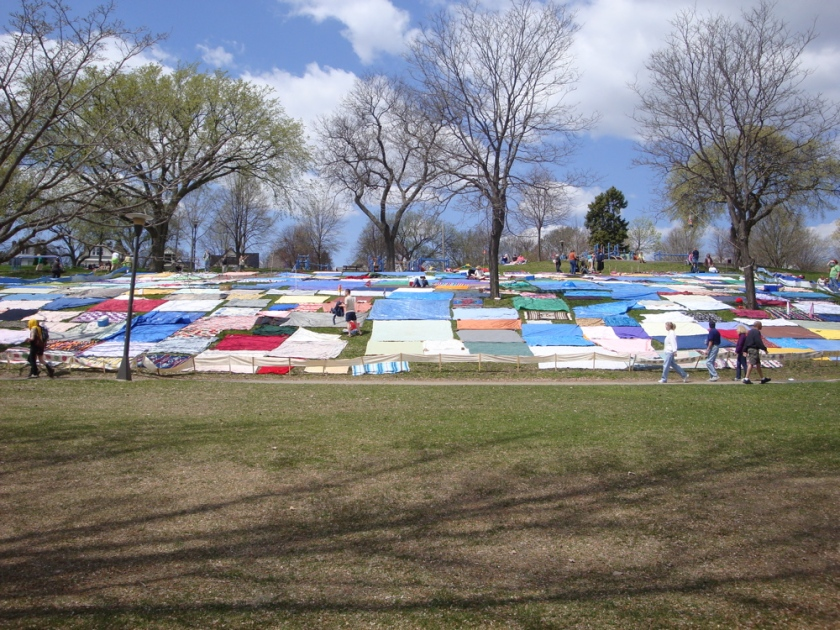 A hillside quilt of blankets awaits bodies for the May Day Pageant.